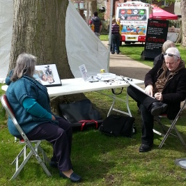 A lady getting her caricature drawn by an artist.