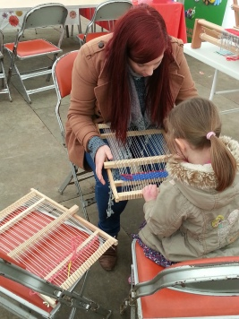 A child learning how to weave.
